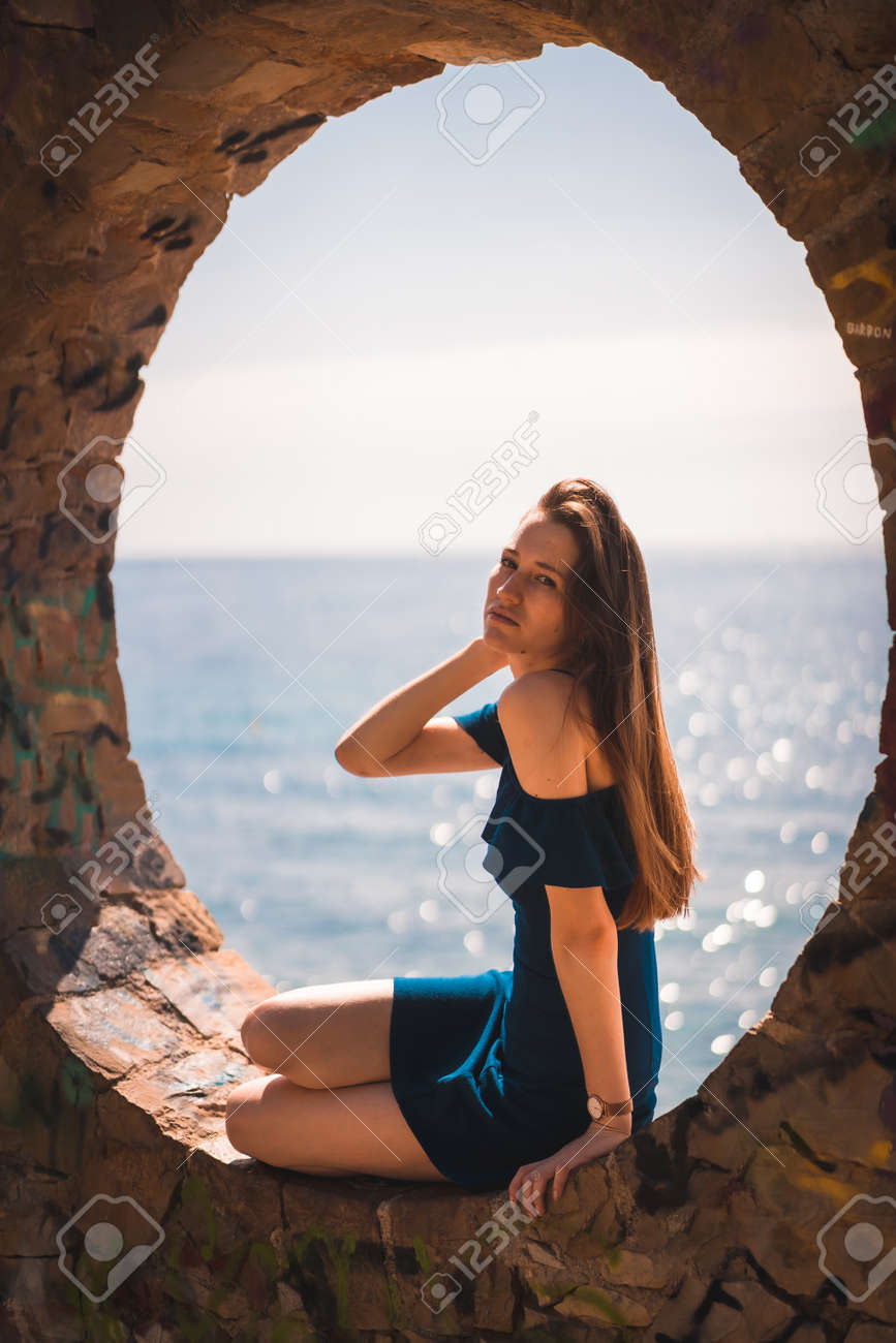 Lifestyle of a young pretty red-haired Caucasian woman sitting in a blue dress by the sea, in a stone window - 167743288