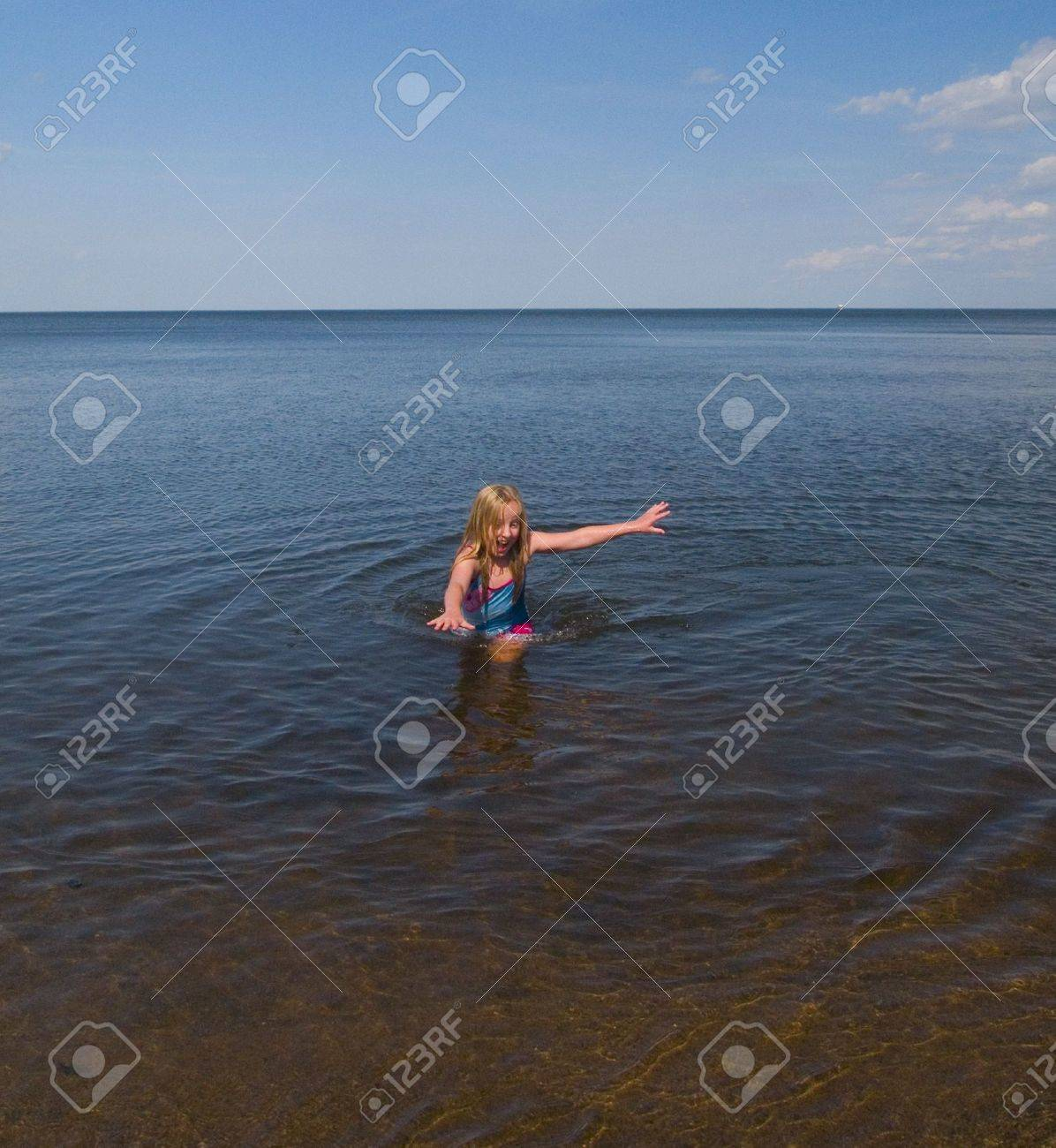 A girl racing to get out of the freezing water of Lake Superior Stock Photo - 3256790
