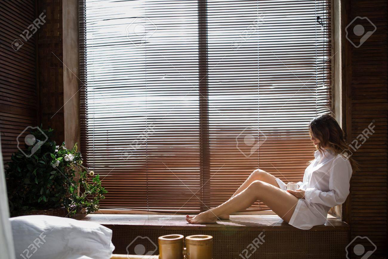 Madchen Durch Das Fenster Auf Der Fensterbank Sitzen Lizenzfreie