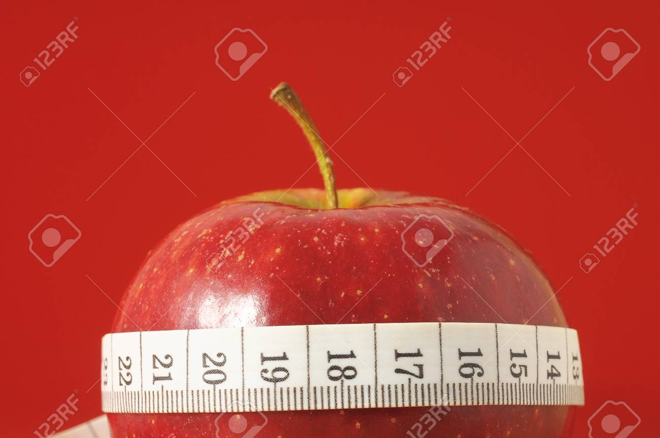 Measuring Tape Wrapped Around A Red Apple As A Symbol Of Diet Stock