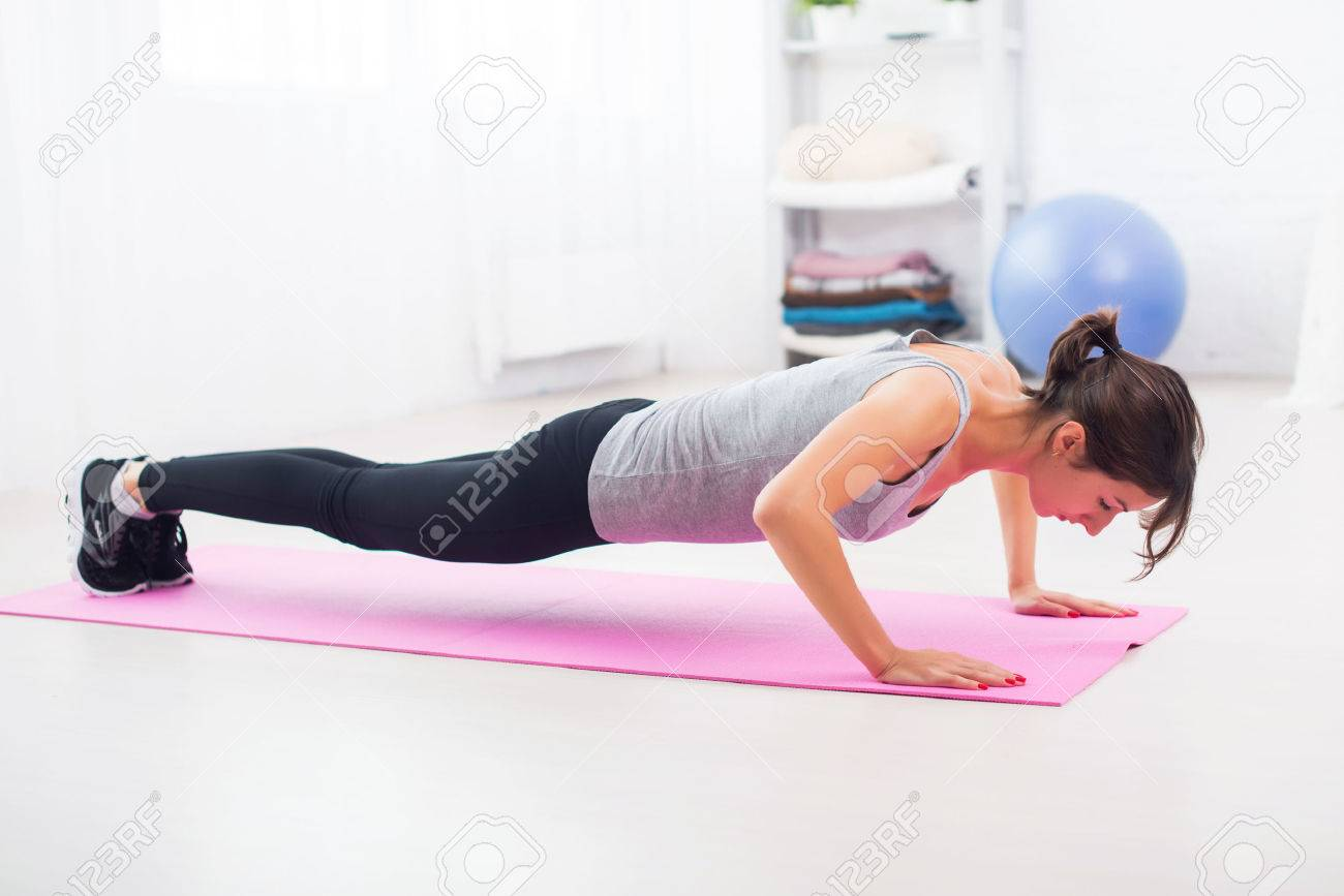 Fit Woman Doing Push Ups On The Floor In Her Living Room An Exercise