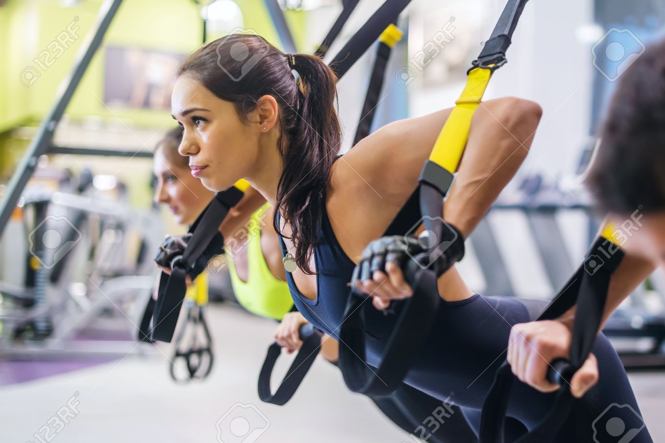 Women doing push ups training arms with trx fitness straps in the gym Concept workout healthy lifestyle sport Stock Photo - 48565581