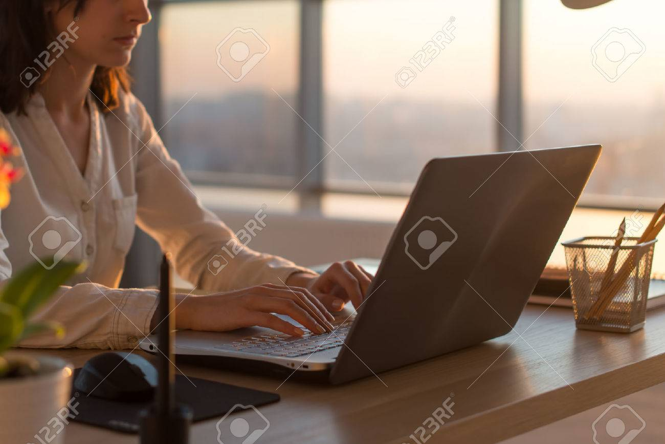 Side view photo of a female programmer using laptop, working, typing, surfing the internet at workplace - 55663765