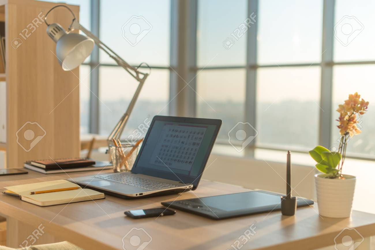 Side view picture of studio workplace with blank notebook laptop. Designer comfortable work table & Side view picture of studio workplace with blank notebook laptop...