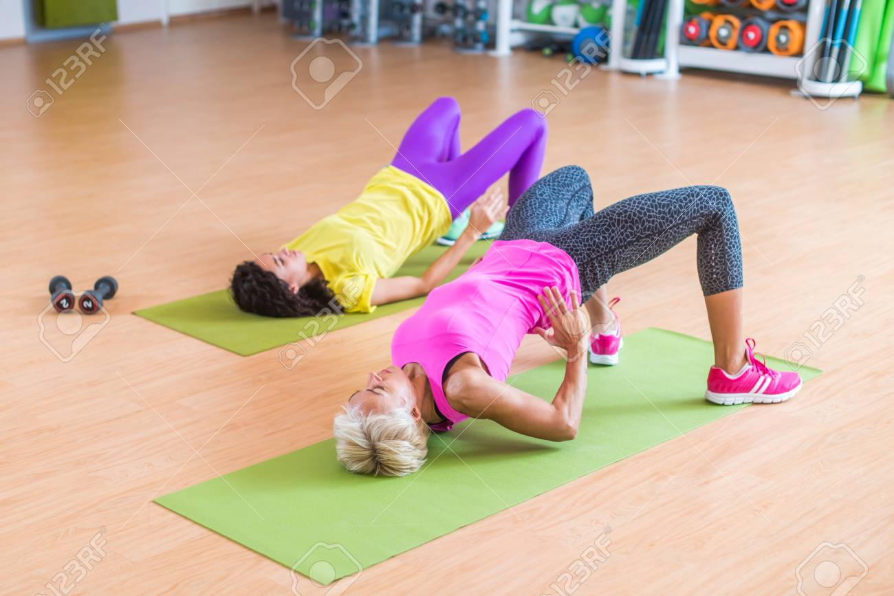 Women training their glutes by doing bridging exercise on mats in gymnasium - 69871003
