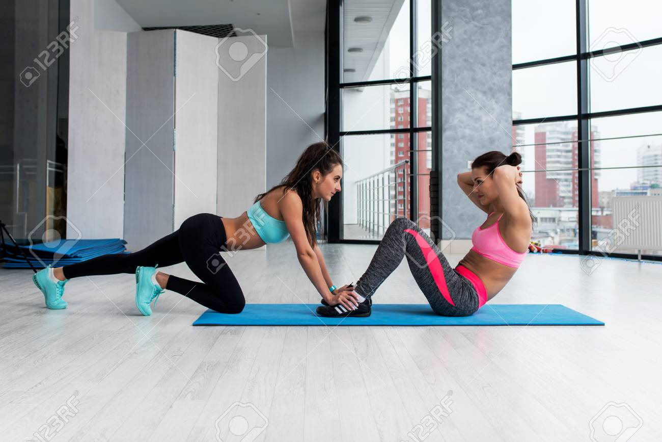Fit Sporty Girl Doing Abs Workout On The Floor In Gym With Assistance