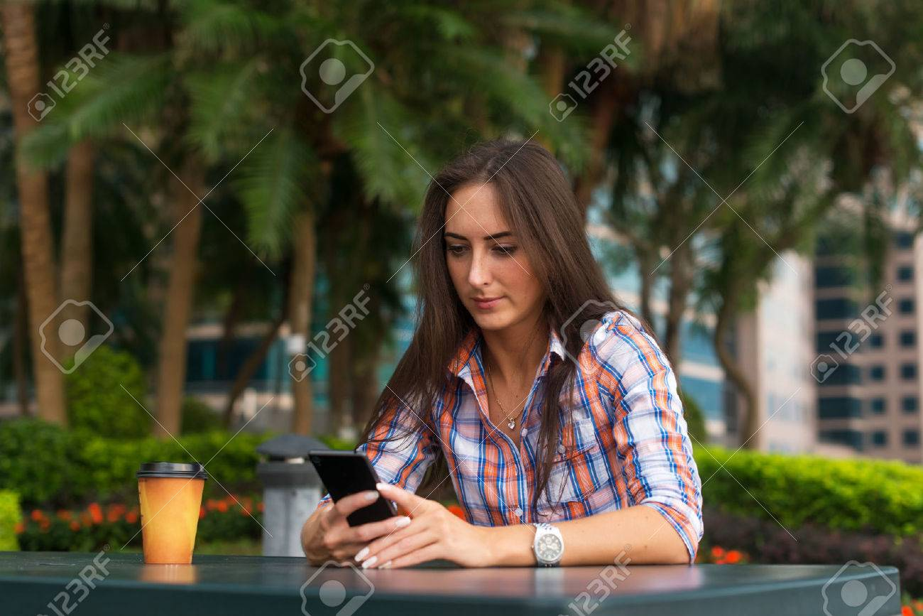 Young woman sitting outdoors reading and typing messages on her smartphone. - 80615726