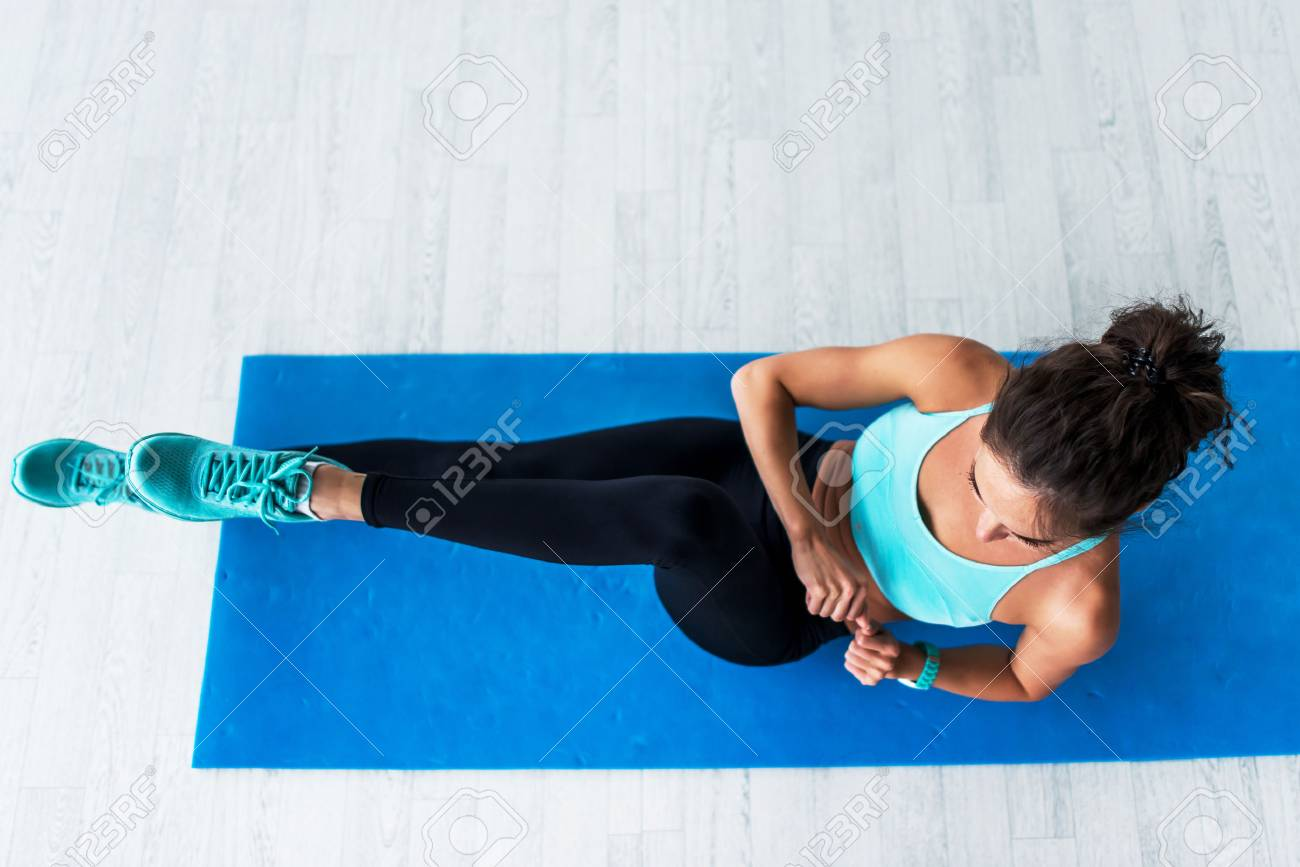 Top view of young fit woman working-out doing bicycle crunches on blue mat indoors. - 82659785