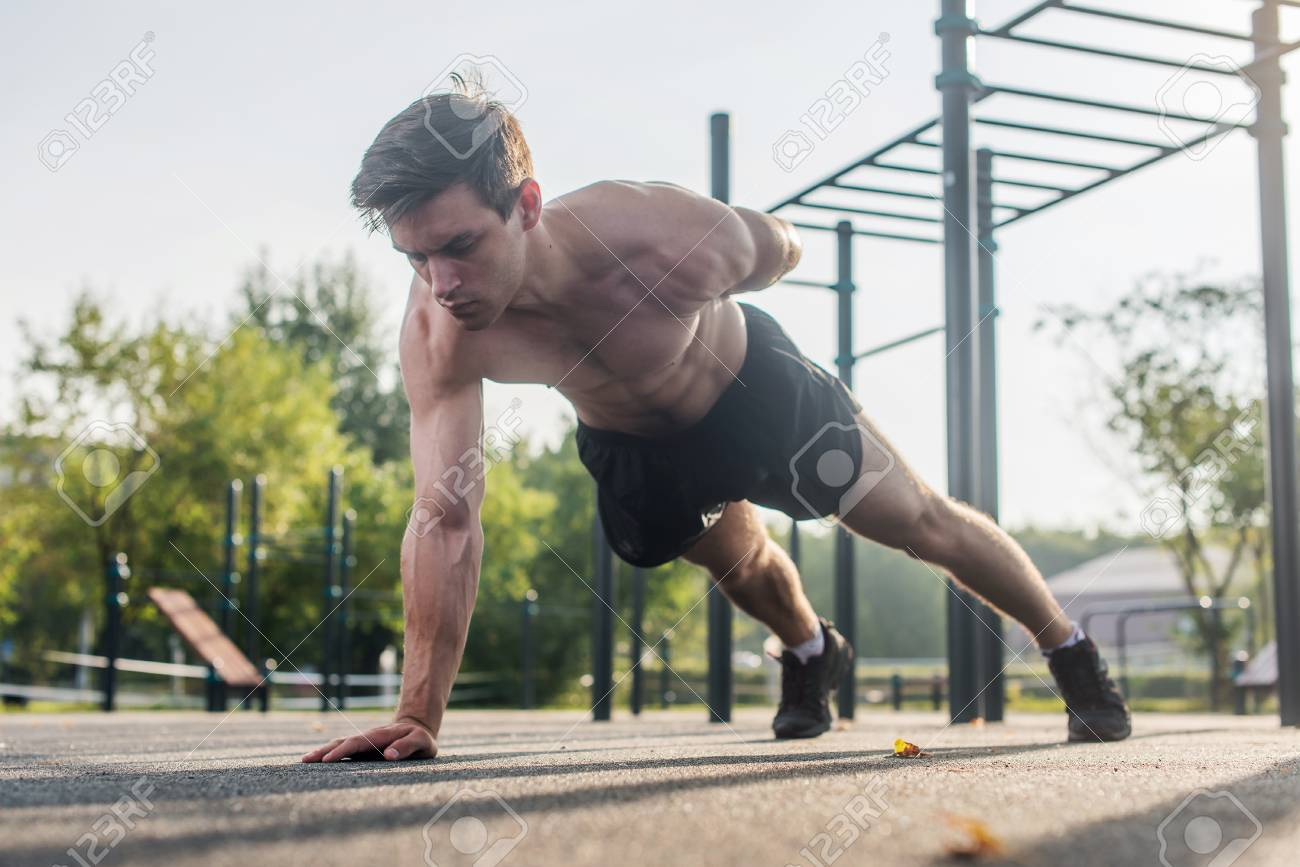Athlete young man doing one-arm push-up exercise working out his upper body muscles outside in summer. - 84119624
