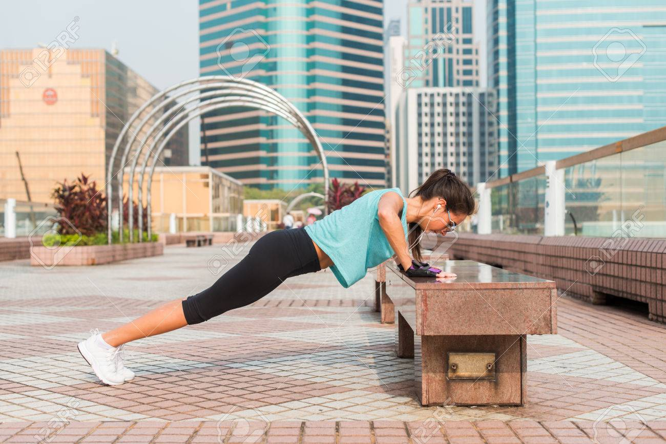 Fitness woman doing feet elevated push-ups on a bench in the city. Sporty girl exercising outdoors - 84049214