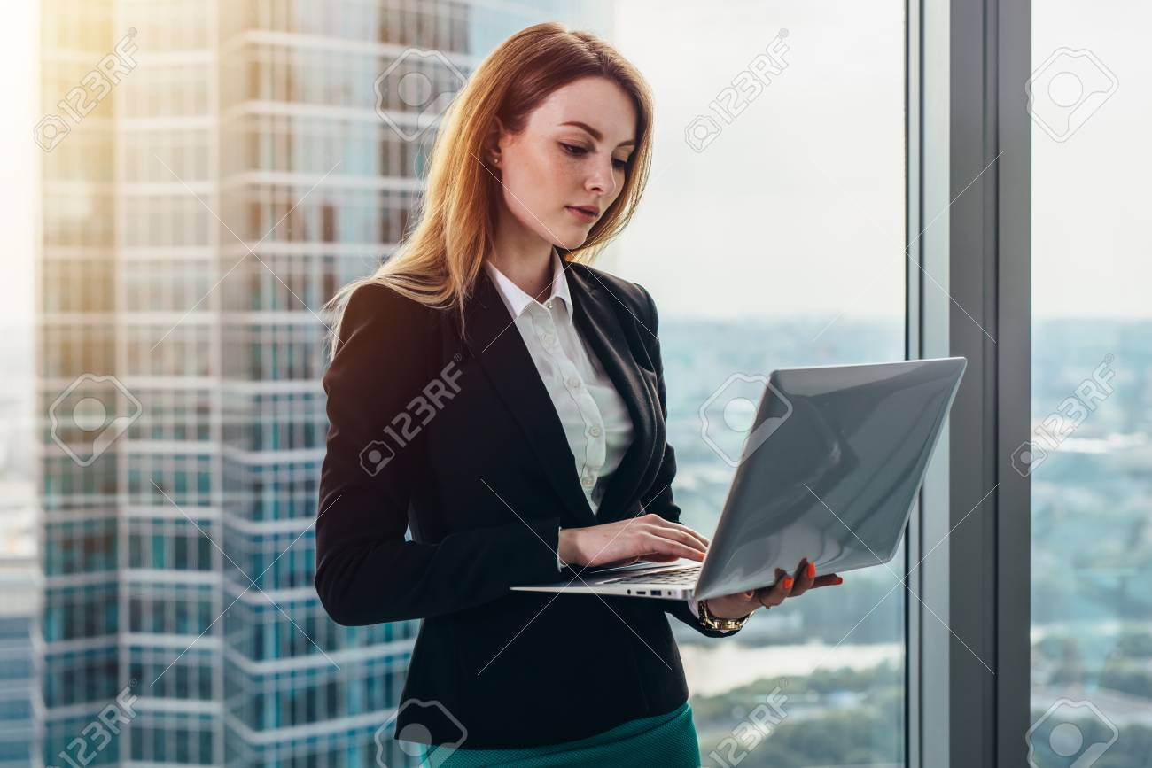 Young female lawyer working in her luxurious office holding a laptop standing against panoramic window with a view on business district - 89095730