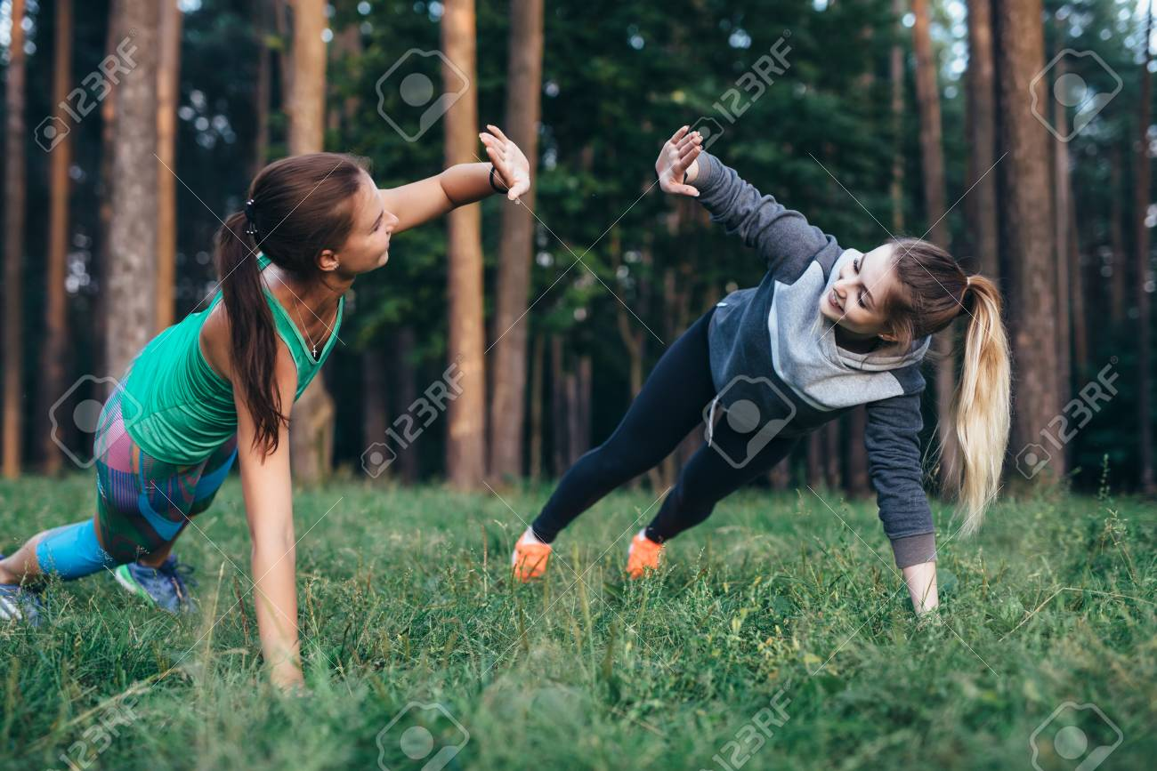 Two female buddies doing partner side plank giving high five while training in the forest - 89095902