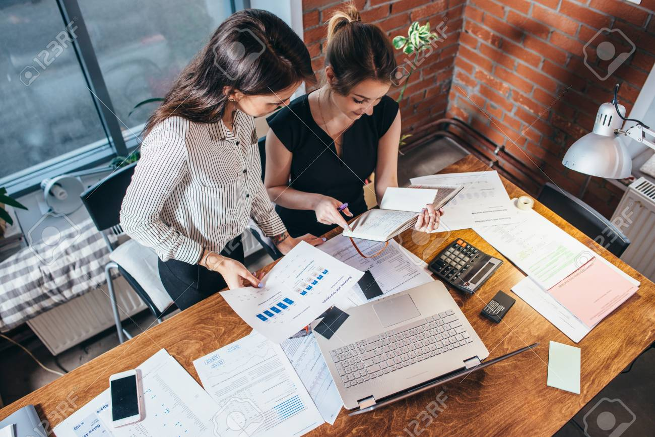 Top view of two female colleagues and desk covered with papers and documents. Businesswomen studying the data working on new sales strategy - 89095998