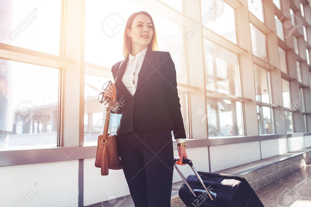 Pretty smiling female flight attendant carrying baggage going to airplane in the airport - 90059352