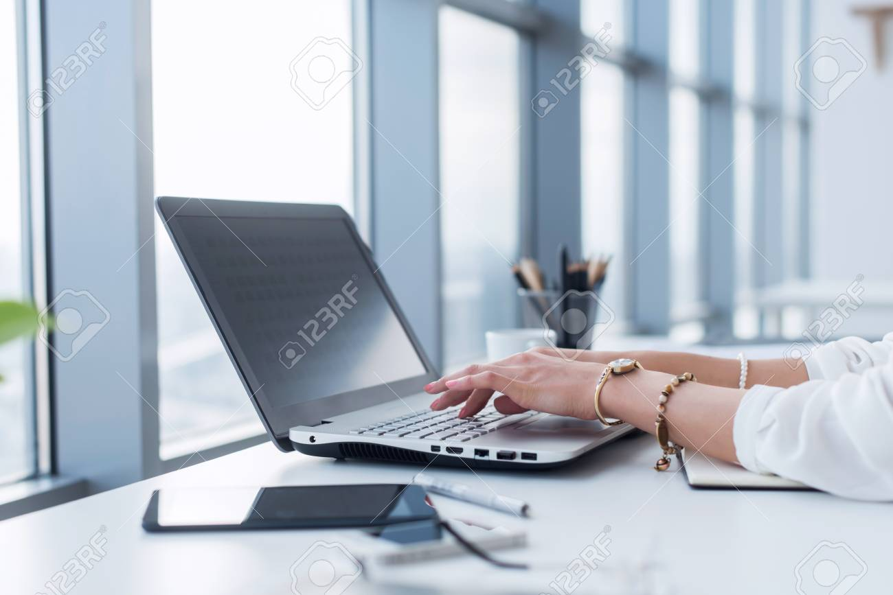Female copywriter at her workplace, home, writing new text using laptop and Wi-Fi internet connection in the morning. - 93049614