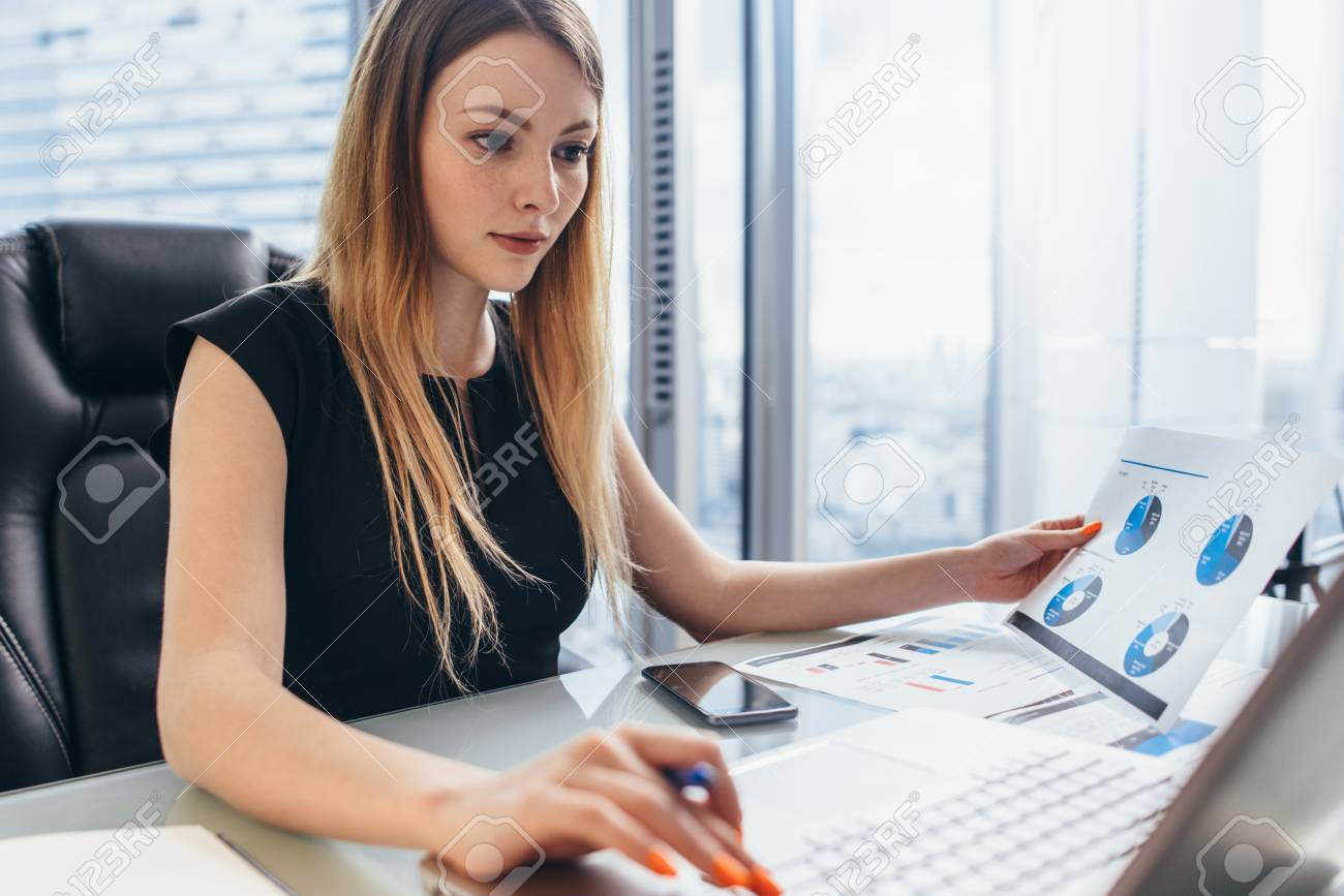 Female director working in office sitting at desk analyzing business statistics holding diagrams and charts using laptop - 93050072
