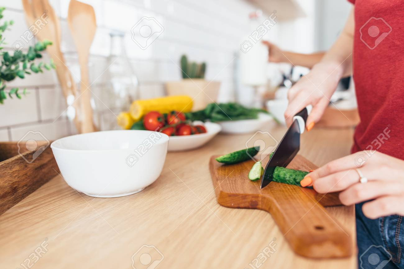 Woman cutting cucumber on the wooden board. - 93882793