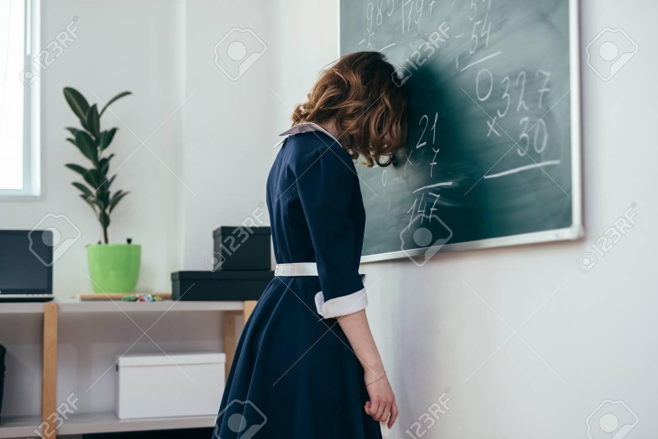 Sad schoolgirl standing in front of blackboard. - 104360654