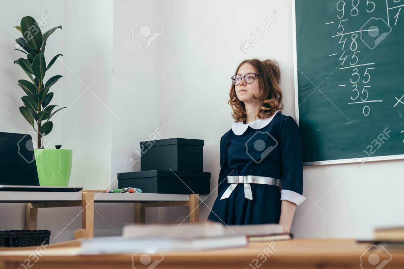 Sad schoolgirl standing in front of blackboard. - 104360657