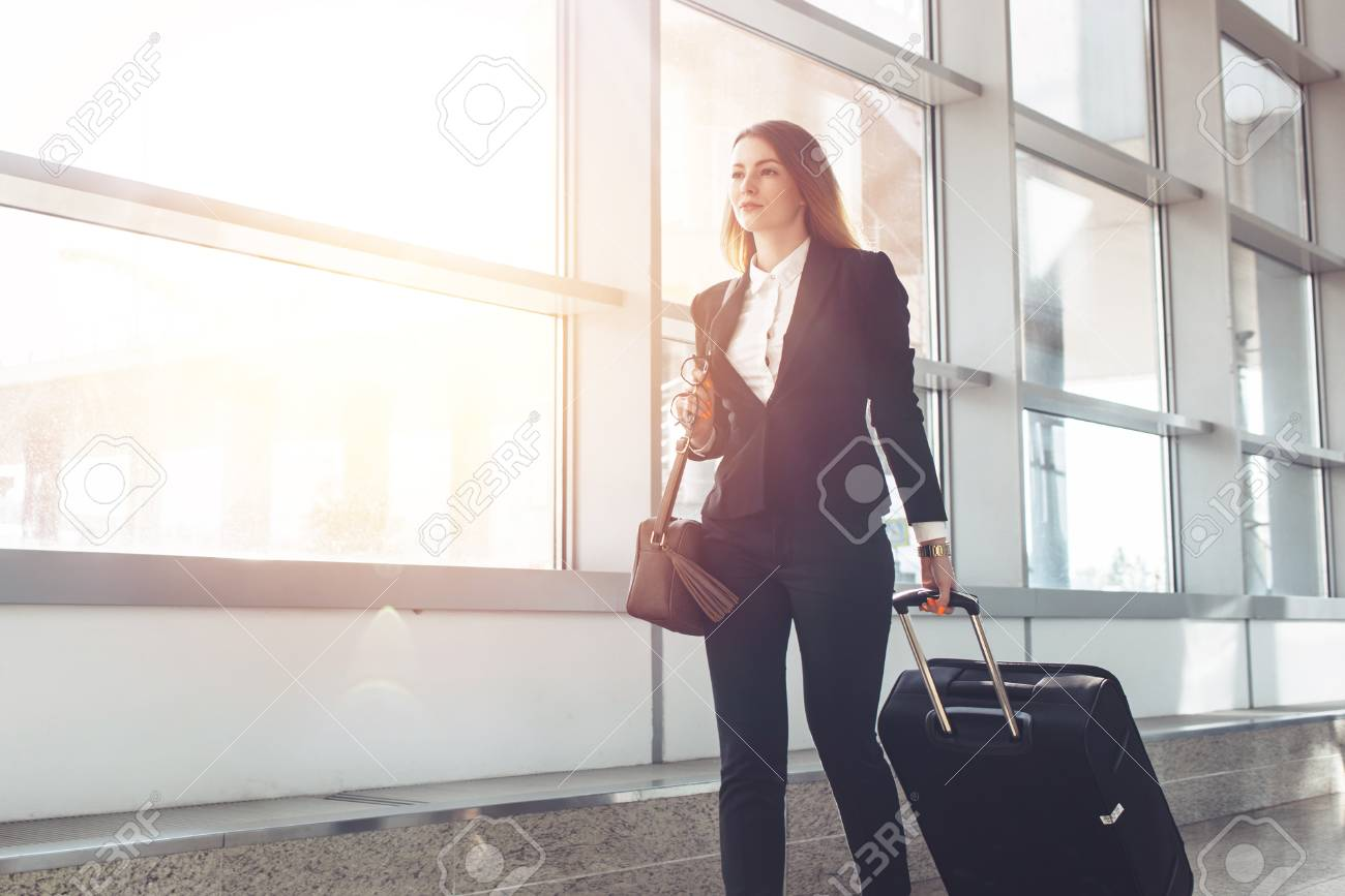 Pretty smiling female flight attendant carrying baggage going to airplane in the airport - 106677379