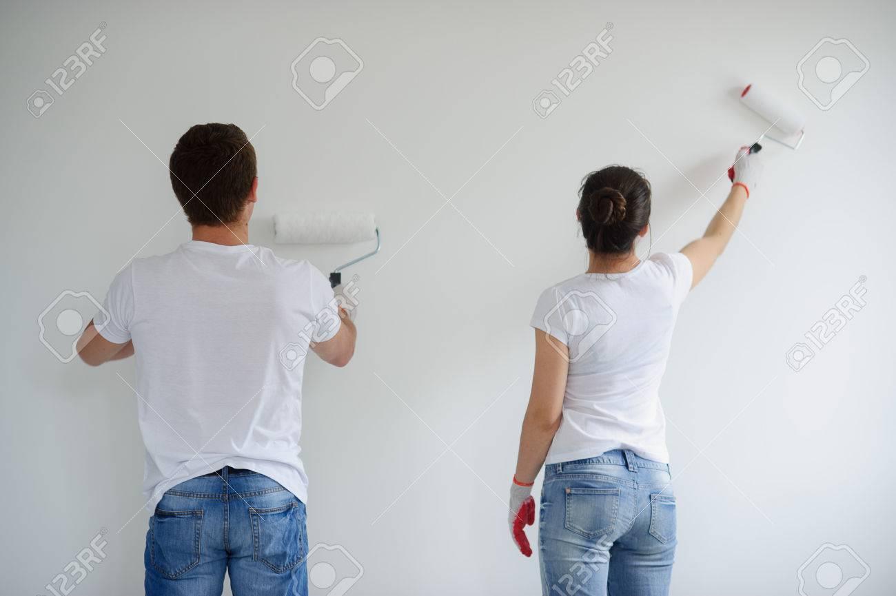 Het jonge paar schildert een witte muur. de jongen en het meisje