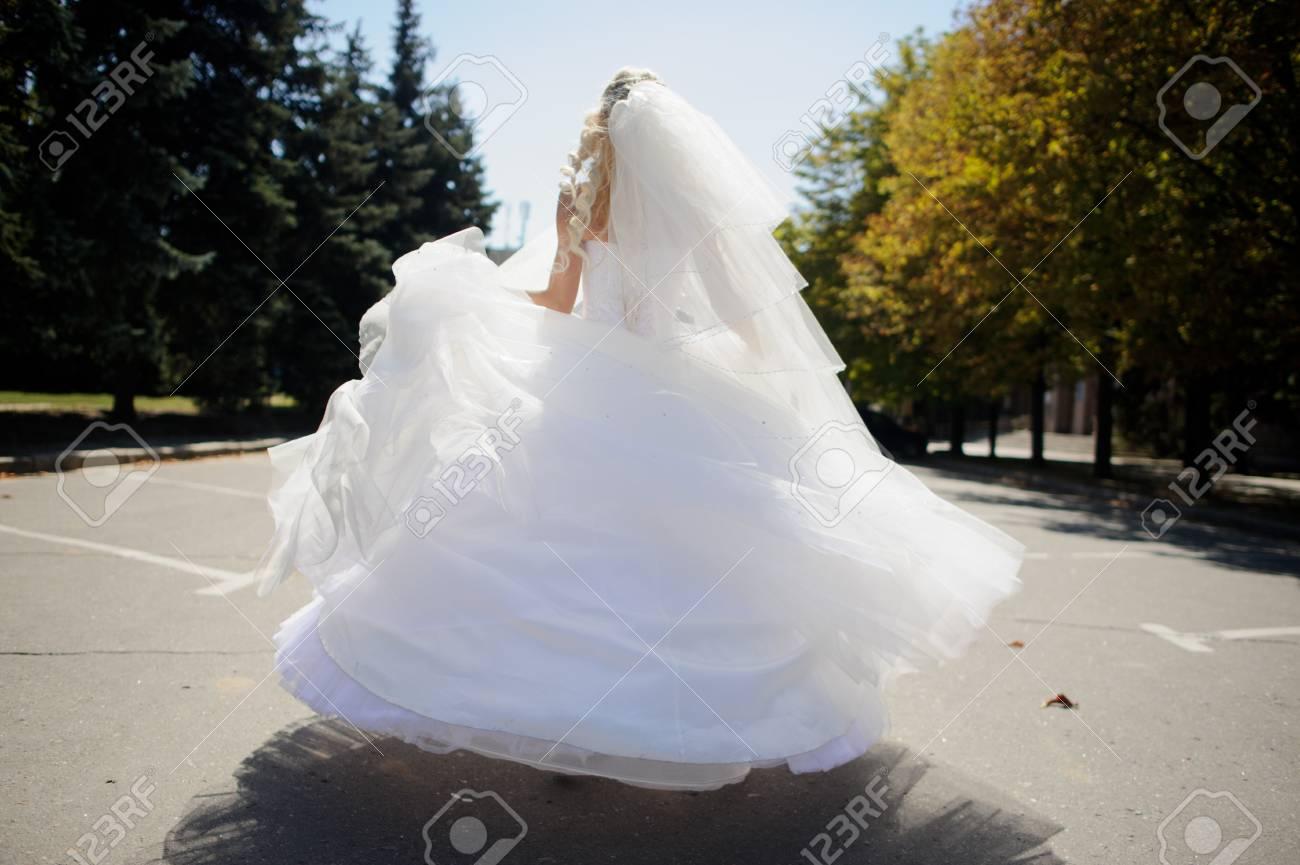 Bride Se Volvió Con Un Magnífico Vestido Blanco Y Velo En El Asfalto Gris Entre Los árboles Del Parque La Esbelta Chica Vestida De Novia Fue Girado
