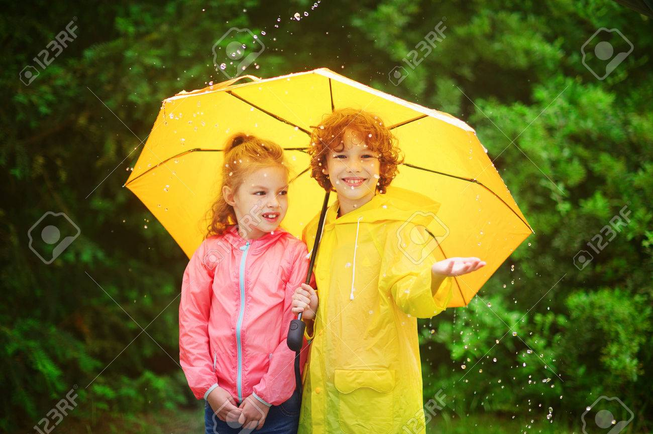 Brother And Sister Stand Together Under A Big Yellow Umbrella The Little Girl Is Dressed