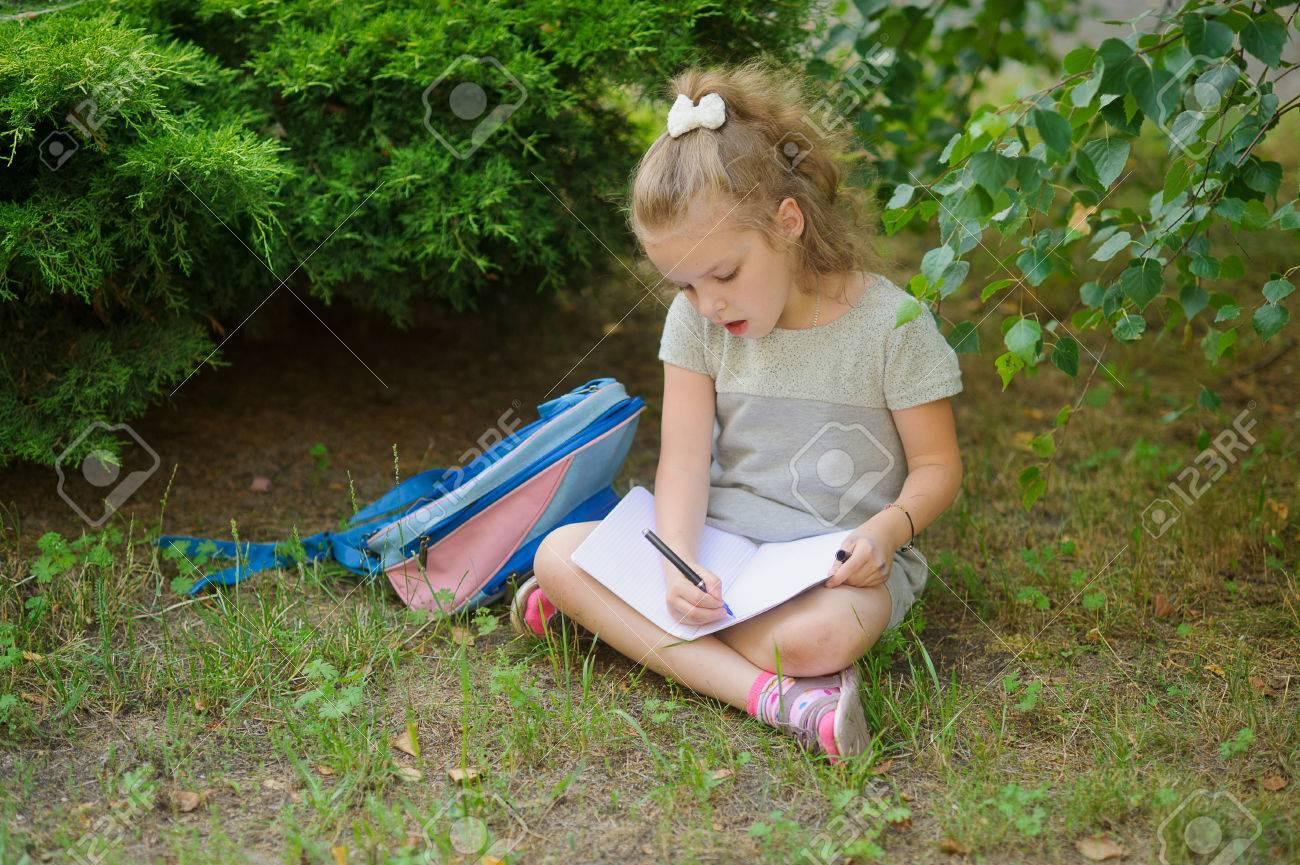 bcd510d0a El primer graduador sienta haber cruzado las piernas debajo de un árbol y  hace los deberes. Femenina tiene una mirada reflexiva. Cerca de la niña su  ...