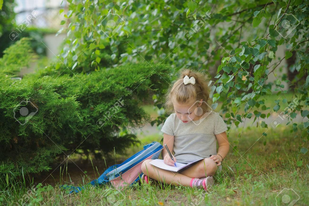 31fad8c81 La pequeña colegiala sienta haber cruzado las piernas debajo de un árbol y  hace los deberes. Femenina tiene una mirada reflexiva. Cerca de la niña ...