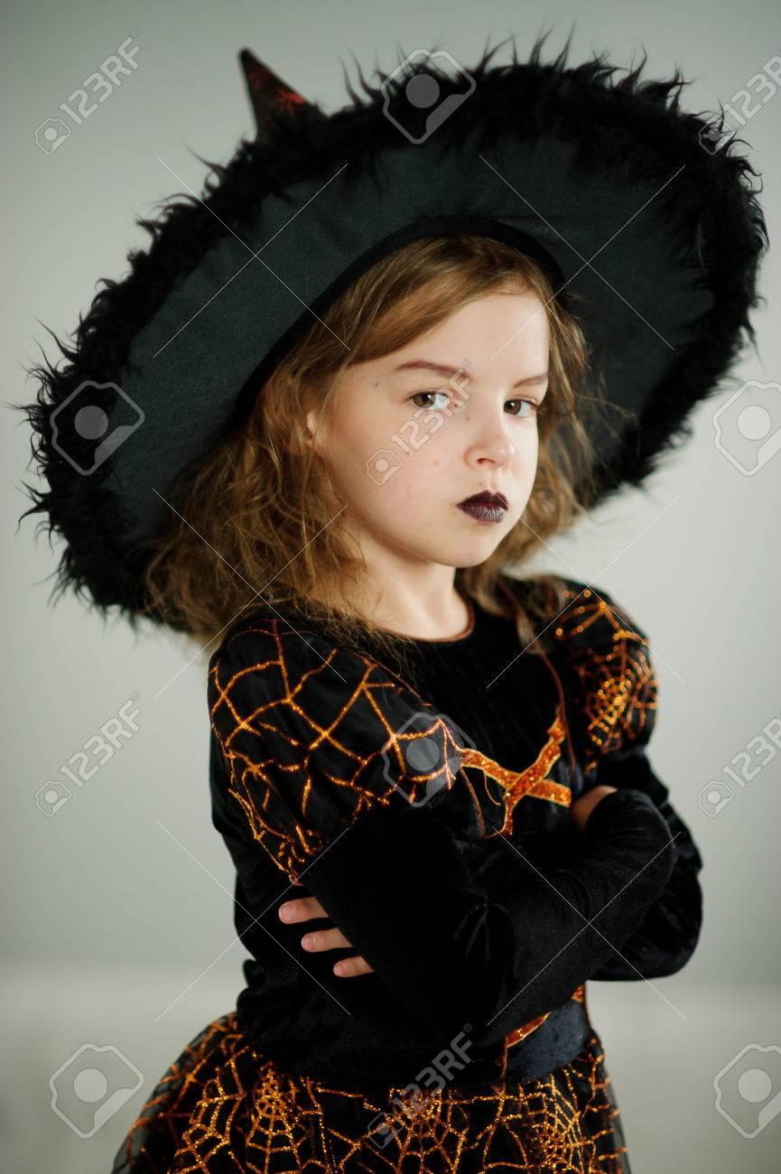 Préparation pour Halloween. Belle fille 8,9 ans montre la sorcière  maléfique. Elle est vêtue d\u0027une robe noire et orange et d\u0027un grand chapeau.  Sur le