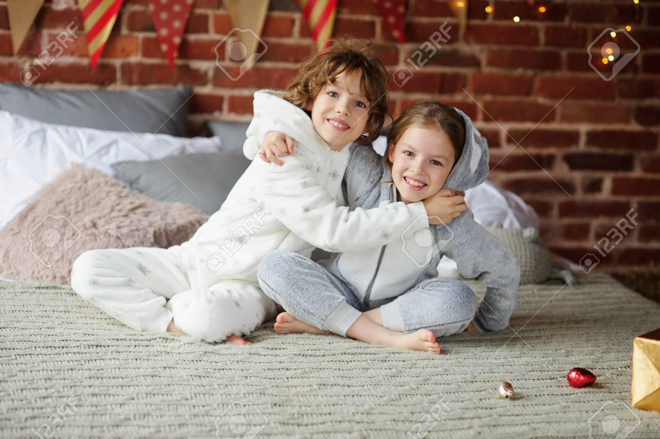 Two Children In Pajamas Sitting On The Bed Waiting For Christmas Gifts. The