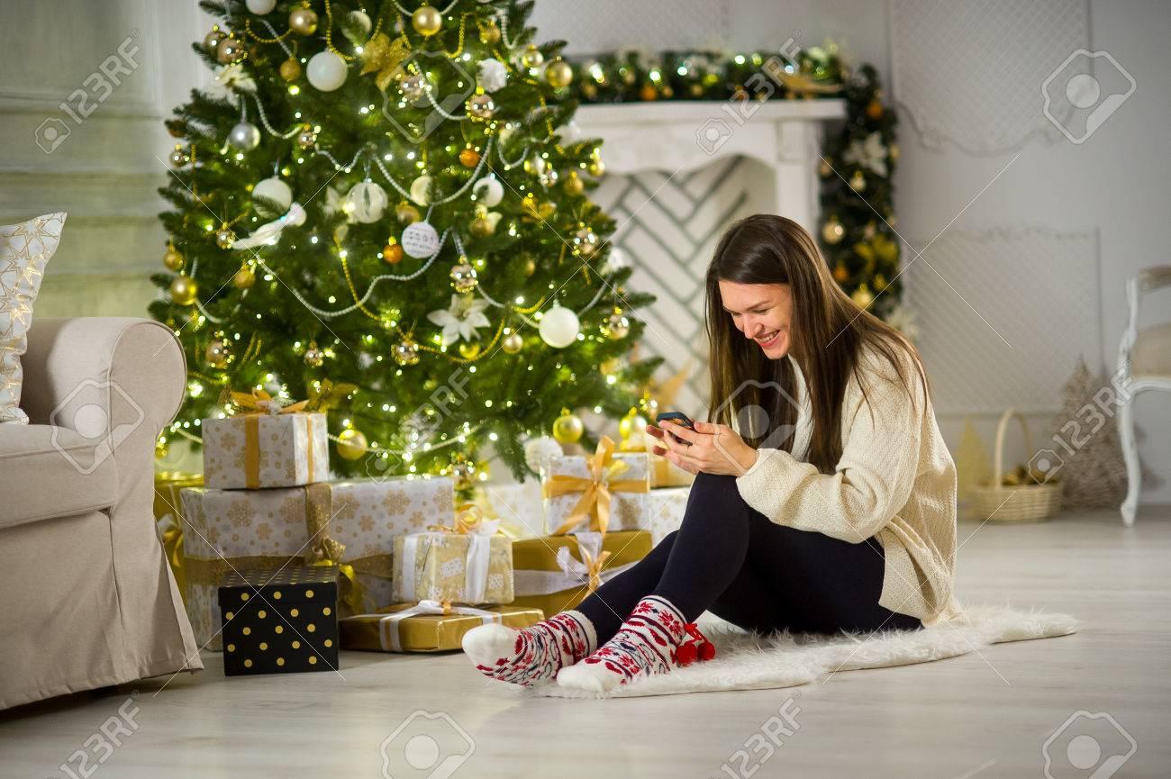 クリスマス ・ イヴ。かわいい黒髪の女の子は、手の中の携帯電話でクリスマス ツリー近くに座っています。家は、休日で飾られています。クリスマス  ツリーの下の多くは美しくギフト ボックスをラップしました。 の写真素材・画像素材 Image 67699504.