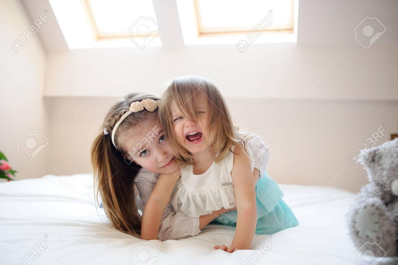 Su Un Grande Letto Due Sorelline Si Trovano In Abbraccio La