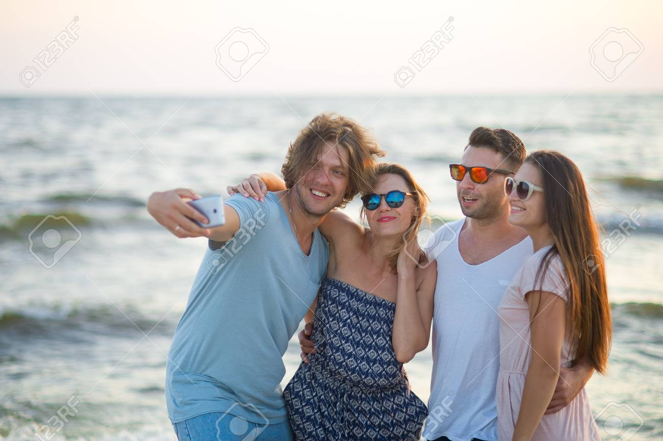 d6b829ad14 Gruppe Nette Junge Leute , Die Auf Dem Strand Fotografiert . Zwei Jungs Und Zwei  Mädchen , Die Auf Einem Hintergrund Von Meereswellen Aufwerfen .