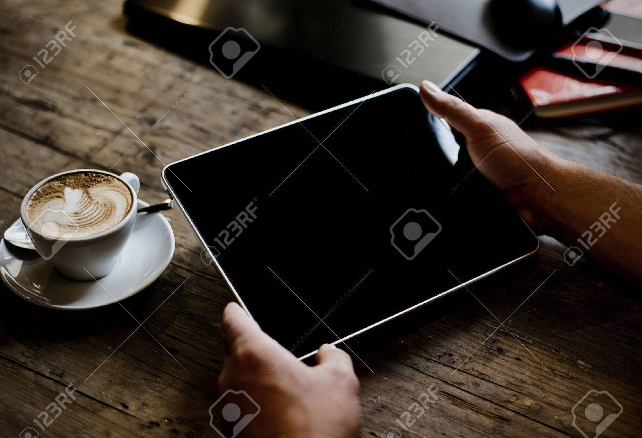 hands of a man holding blank tablet device over a wooden workspace table - 25210468