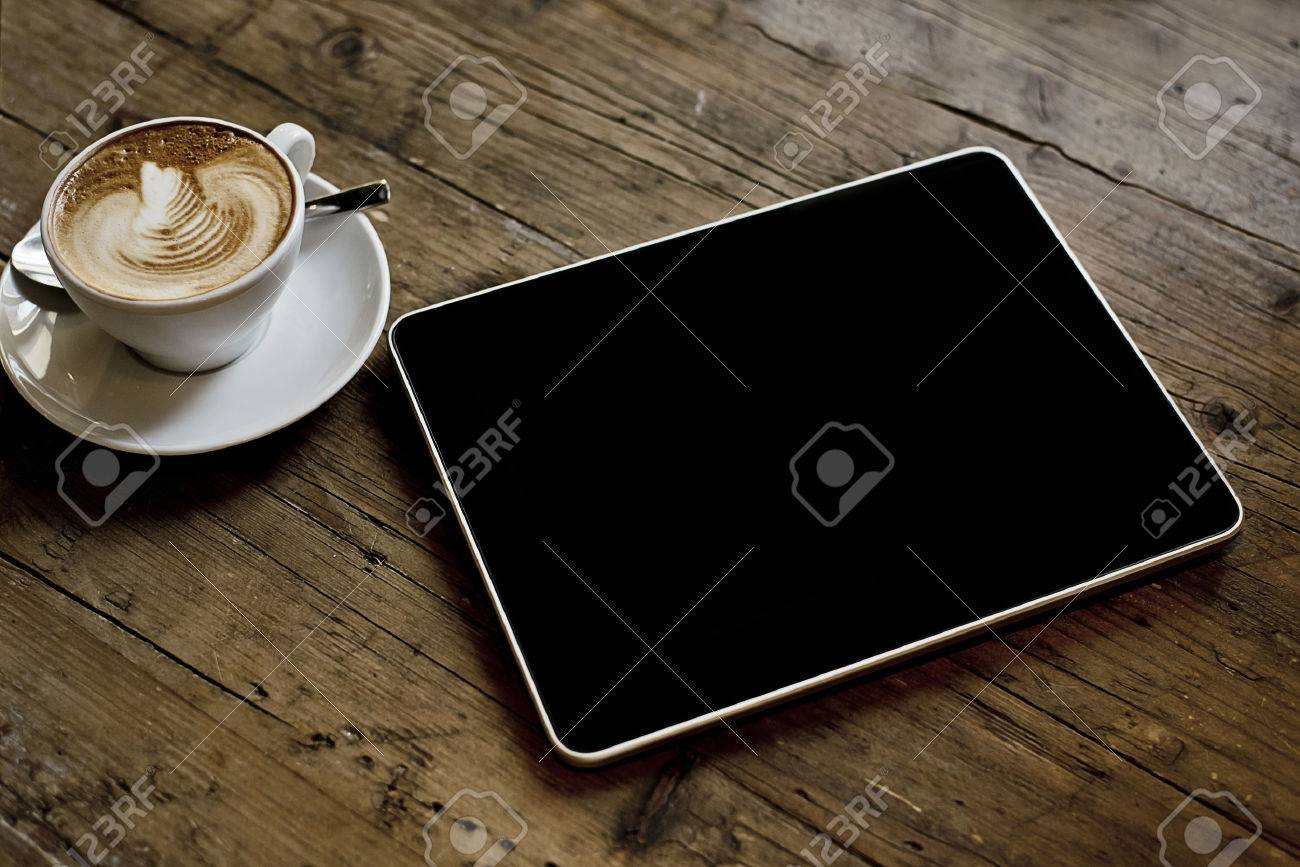 blank tablet computer on a wooden background next to a cup of coffee - 25210467