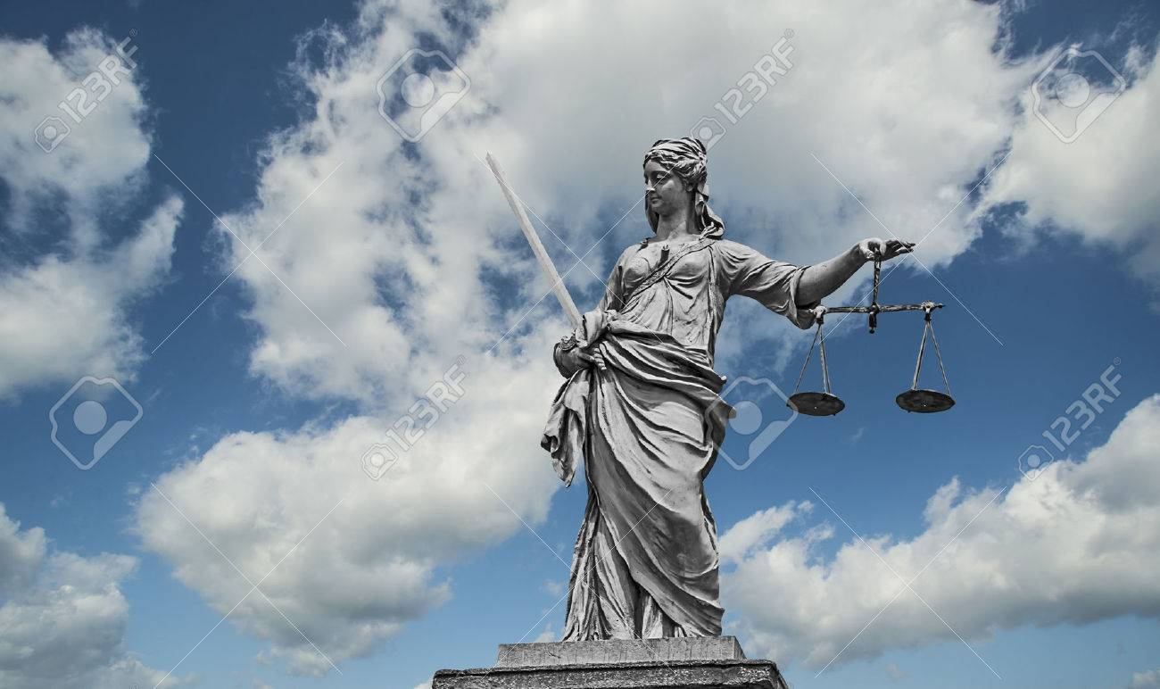 Statue of Lady Justice holding scales and sword in front of a blue cloudy sky - 47621121