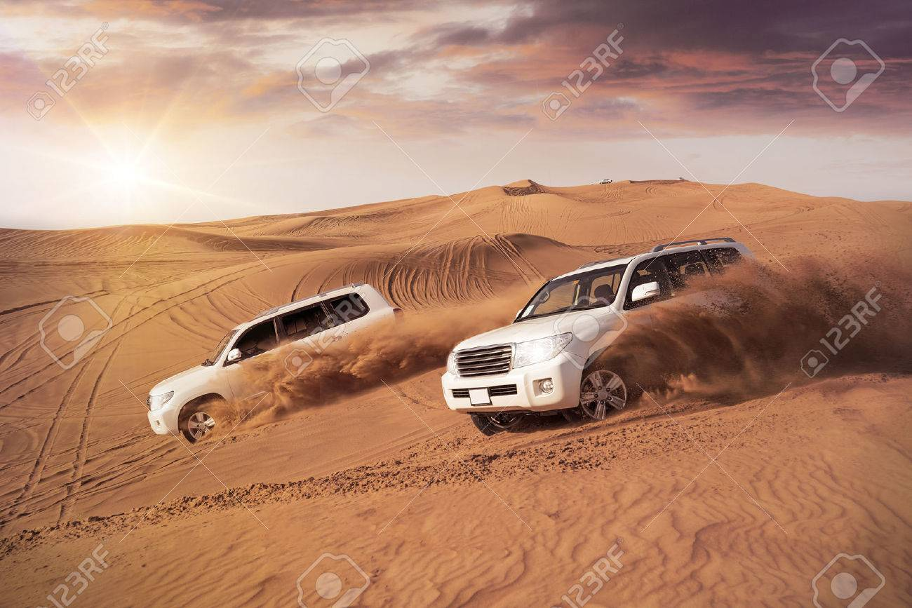 two 4x4 vehicles bashing side to side through the desert dunes in the evening sun - 54905518
