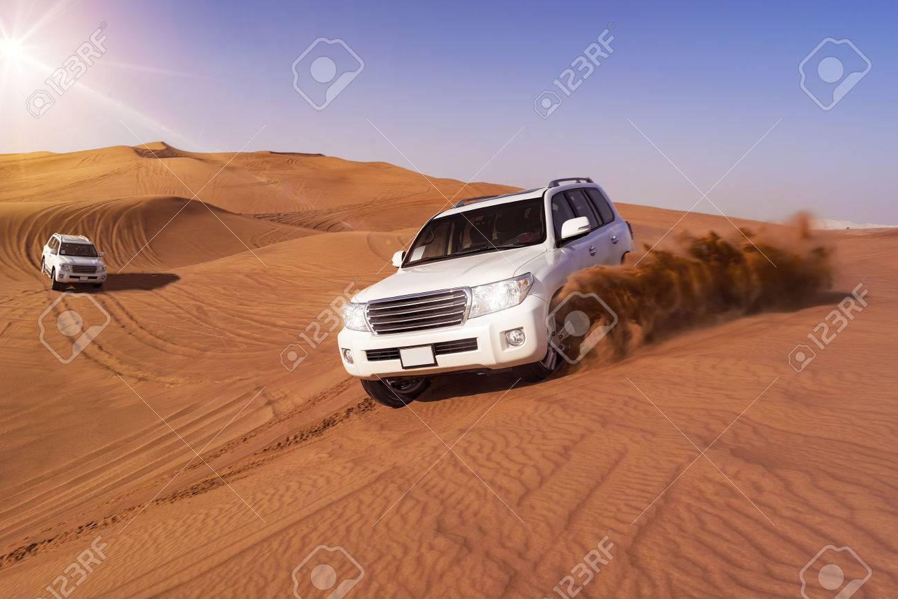 Desert SUVs bashing through the arabian sand dunes - 54905569