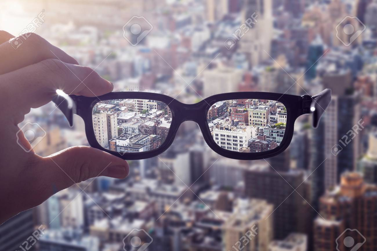 5263e594f3 cityscape focused in glasses lenses with hand holding the eyewear between  thumb and index finger Stock