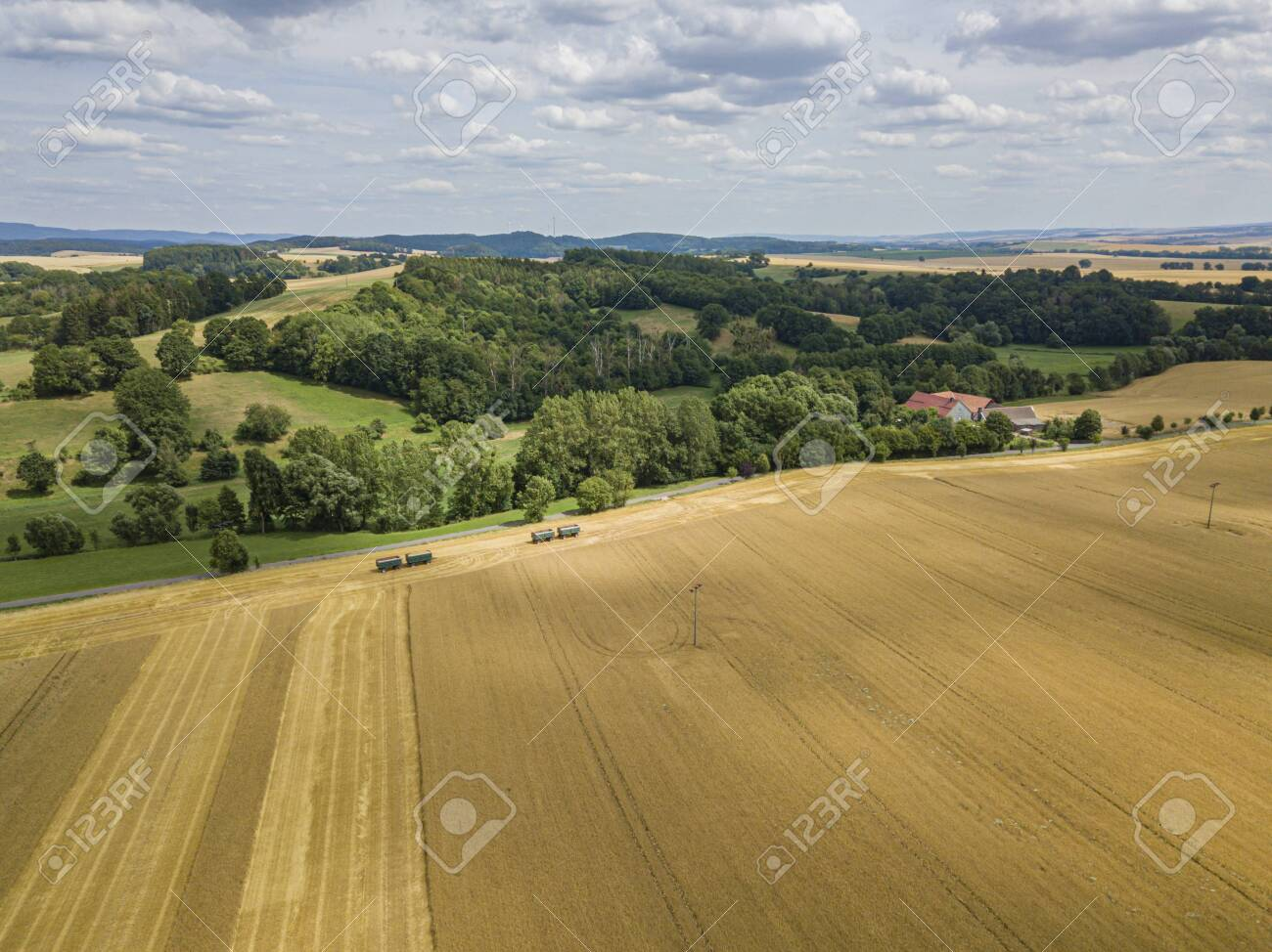 Aerial view of a crops field with forest and hills in the back - 132455737