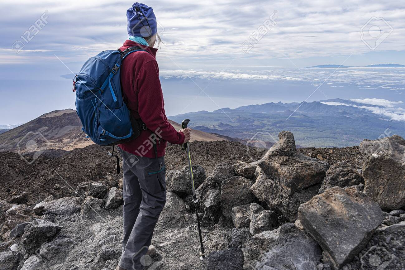 full equipped senior hiker standing on a rocky mountain top with scenic view - 137352617