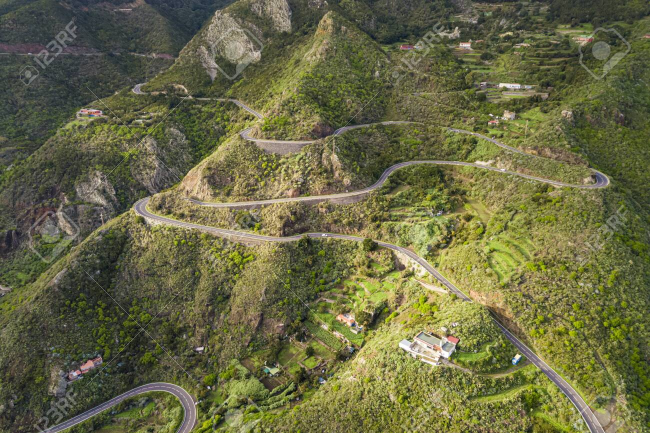 Aerial view of a winding road along a large mountain - 137602210