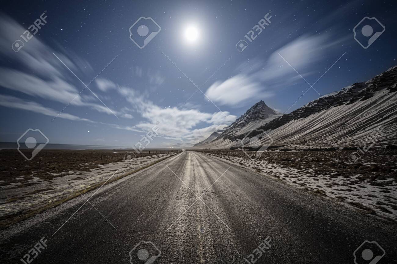 straight country road under the moonlight with dramatic clouds and starry sky, Iceland - 146780999