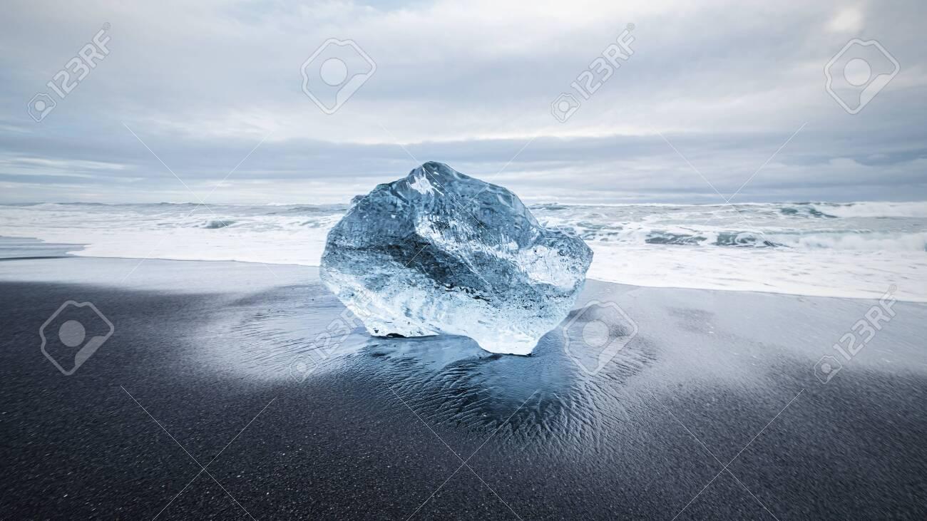 blue ice diamond on black lava sand beach near Jökulsárlón Glacier Lake, Iceland - 146781007
