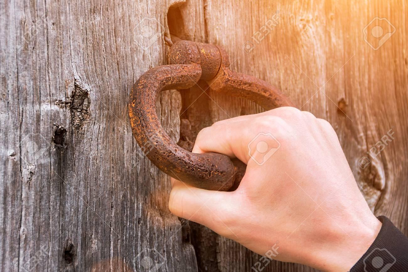 Old bell at the door, hand knocks on the wooden door - 101735416