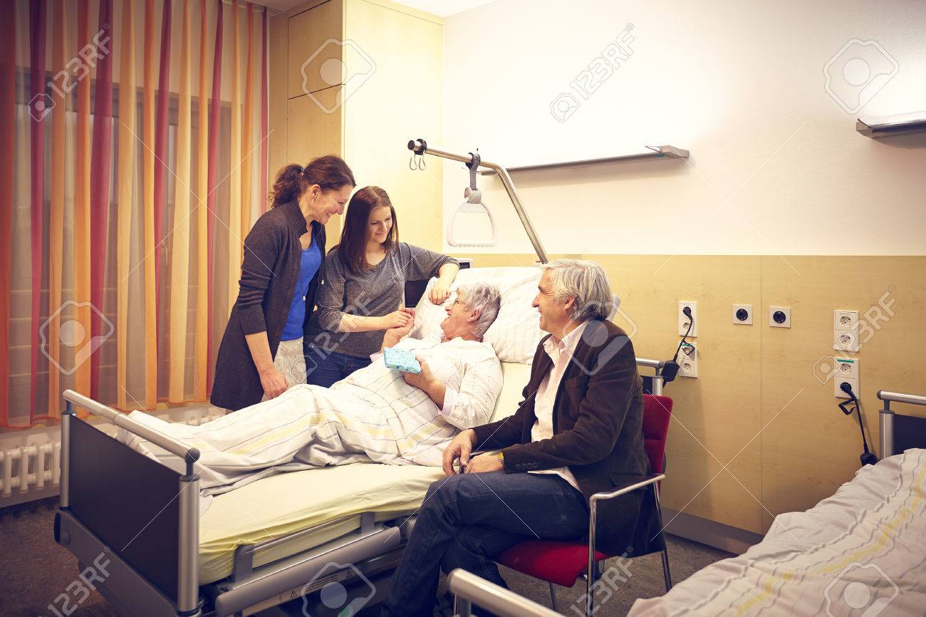 Hospital room with patient and family - Hospital Visit Family With Patient In Bed Stock Photo 28104037