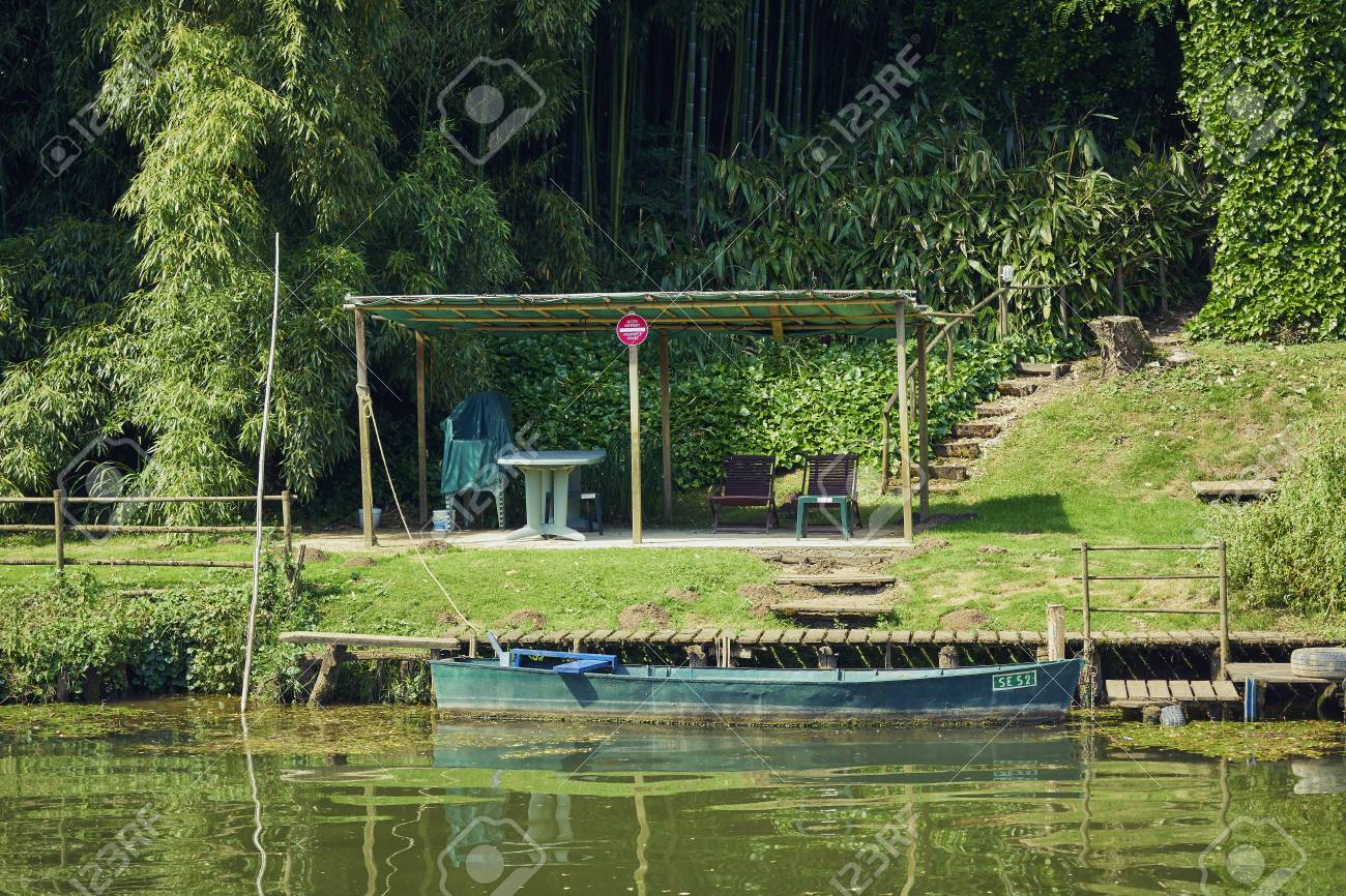 Rowing boat in front of a pergola lies on the bank of a canal