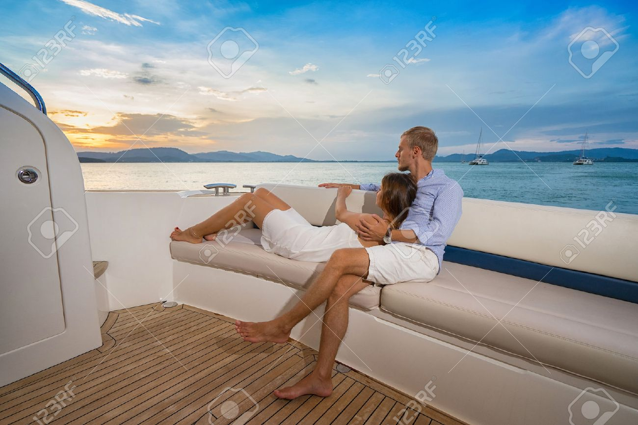 Romantic vacation . Beautiful couple looking in sunset from the yacht - 52343907