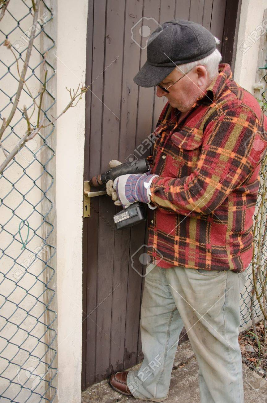 senior male repairing a wooden door latch with drill Stock Photo - 5240891